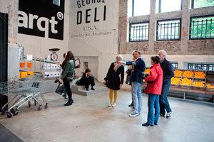 Ondernemers bekijken op de fiets etalages in Amsterdam