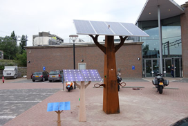 Boom met zonnecellen voor opladen e-bikes