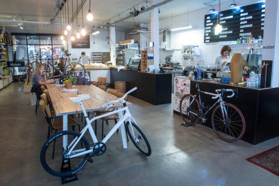 De grote leestafel met rechts de toonbank voor koffie en lunchgerechten en achterin de bakkerij.