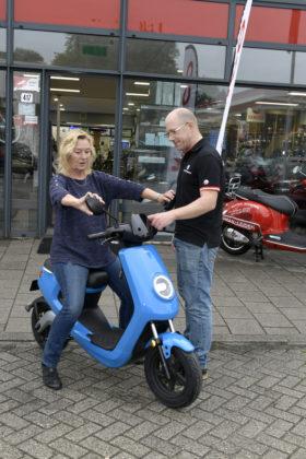 Bedrijfsleider Richard Verweij laat een klant proefrijden op een e-scooter. Foto Fotoburo Dijkstra